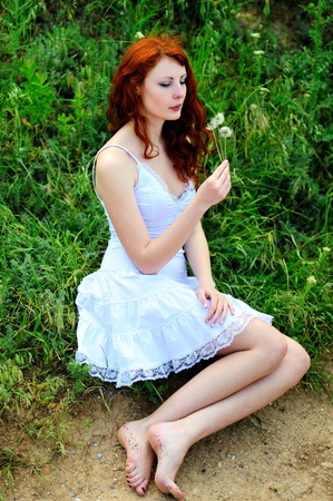 Cute redhead girl who was blowing on a dandelions in her hands. photo