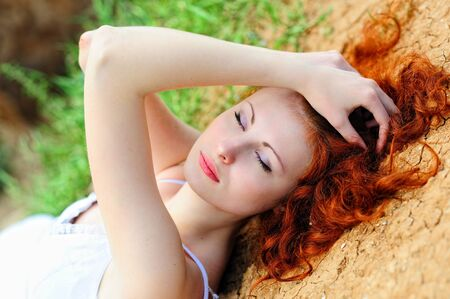 pressure loss: Beautiful young woman with red hair laying on the ground. Stock Photo