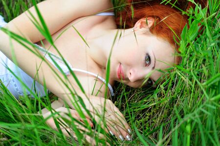 Cute young redhead female lying on grass field at the park.  photo