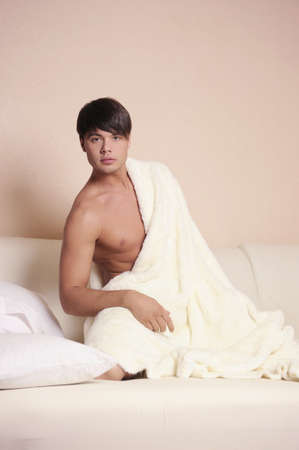 Young sexy man sitting on a bed. Stock Photo - 9833001