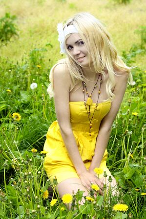 Beautiful young girl with long blond hair, dressed in a yellow dress sitting in field with camomiles. Stock Photo - 9999659