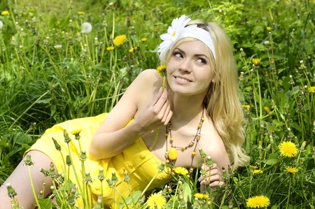 Beautiful young girl with long blond hair, dressed in a yellow dress lying in field with camomiles. photo
