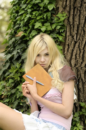 Young beautiful upset girl with book sitting on grass in park. photo