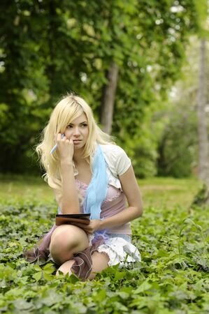 Young beautiful upset girl with book sitting on grass in park. Stock Photo - 9999655