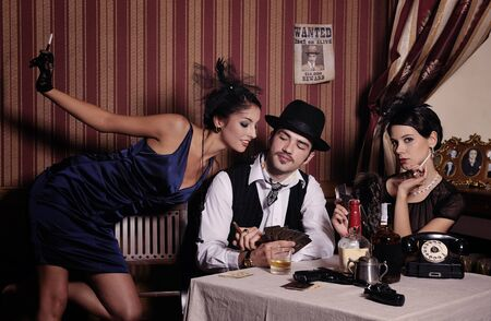 Gambling mafia type with cigarette, playing poker, picture in retro style. Focus on  man. photo