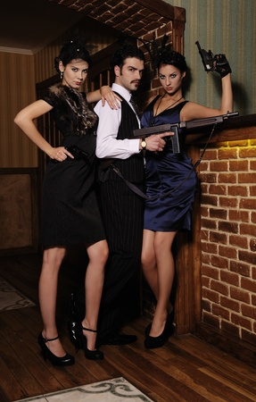 jealousy: A guy and two beautiful young women in the image of gangsters with guns.