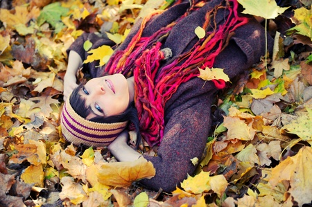 Happy brunette girl lying in autumn leaves. Outdoor. Stock Photo - 10354142