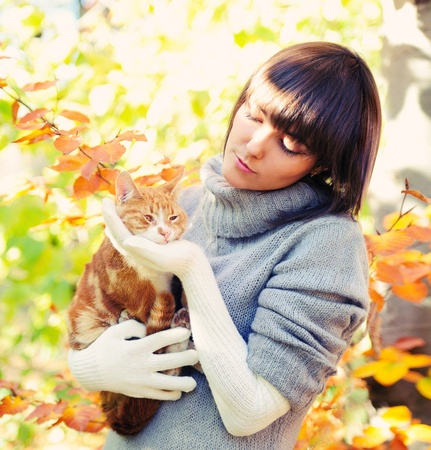 autumn cat: Happy girl portrait playing with ginger cat, autumn outdoor.  Stock Photo