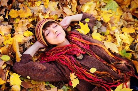 caras felices: Sonriendo retrato de chica feliz, tumbado en el oto�o de hojas. Al aire libre.