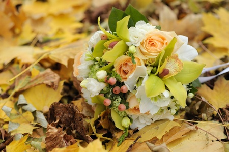 Wedding bouquet on bright autumn leaves in park. Soft focus. photo