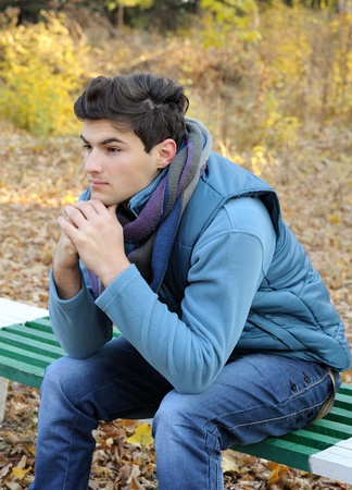 Young stylish man portrait sitting in autumn park. Outdoor. photo