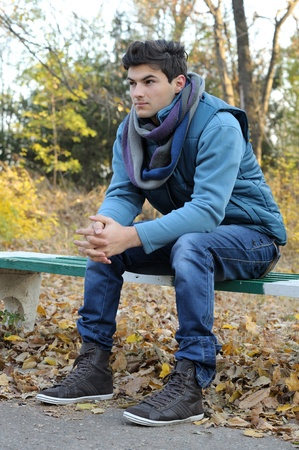 stylish boy: Young stylish man sitting in autumn park. Outdoor.