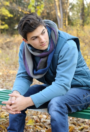 hot boy: Young stylish man portrait sitting in autumn park. Outdoor. Stock Photo