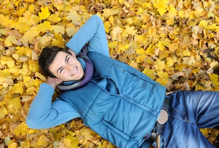 lying in leaves: Young smiling man portrait laying in foliage in autumn park. Outdoor.