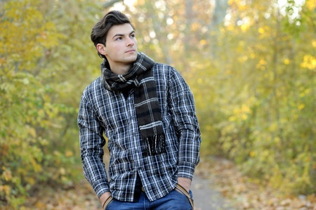 Young stylish man portrait in autumn park. Outdoor. photo