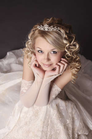 Portrait of a beautiful smiling woman dressed as a bride over gray background  photo