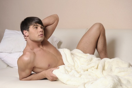 Young sexy man lying on a bed. Stock Photo - 12964686