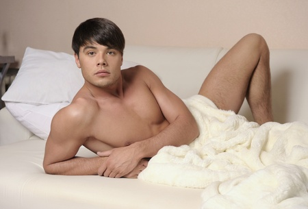 Young sexy man lying on a bed. Stock Photo - 12964685
