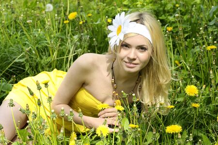 Beautiful young girl lying in field with camomiles. photo