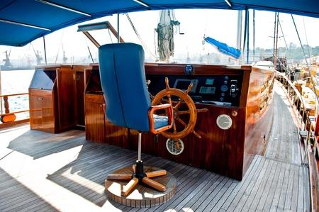 caba�a: Cockpit dentro de un barco con una rueda de madera y sill�n de cuero