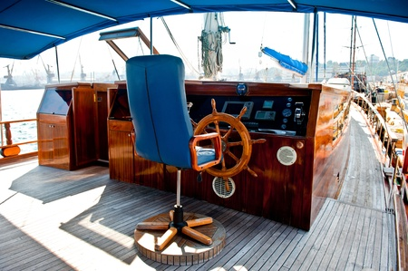 Cockpit inside a boat with a wood wheel and leather chair  photo