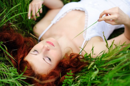 red grass: Resting girl portrait, lying in grass field  Outdoor   Stock Photo