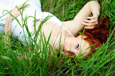 Smiling happy girl portrait, lying in grass field  Outdoor   photo