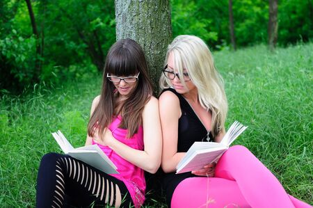 Two beautiful student girls reading books in park. photo
