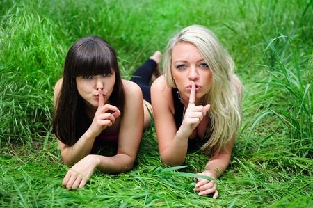 Two beautiful young women friends talking secret. Outdoor. photo