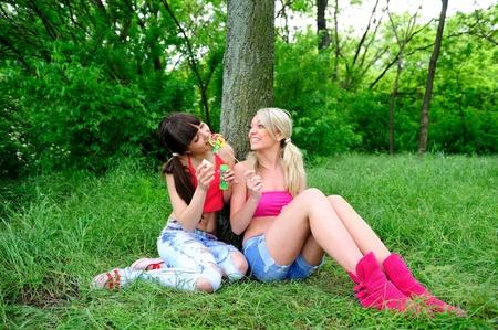 Two beautiful young women friends having fun outdoor. photo