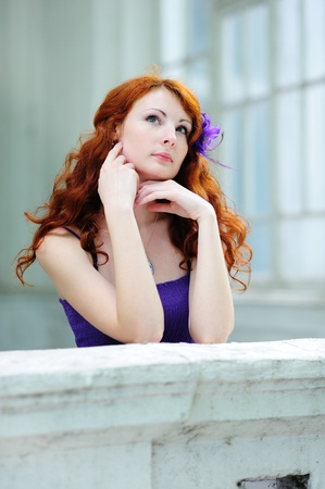 Young beautiful redhead woman portrait standing on balcony. photo