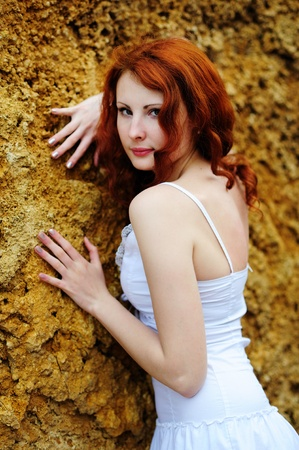 Young redhead sensual woman portrait standing near the rock. Outdoor. photo