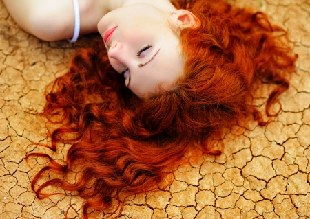 Beautiful young woman with red hair on the dried up ground  Stock Photo