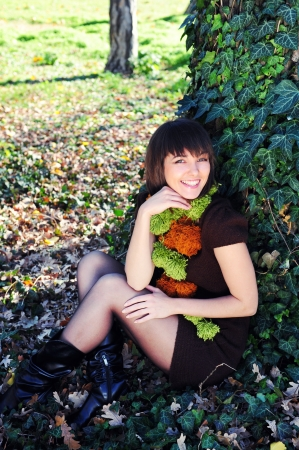 Smiling happy woman sitting under a tree in the autumn park  photo