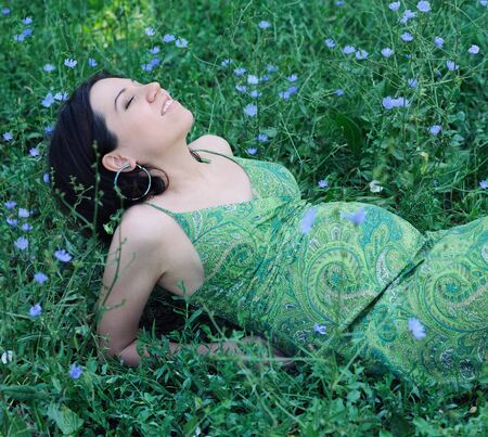 Beautiful pregnant woman relaxing on grass. Stock Photo - 17543609