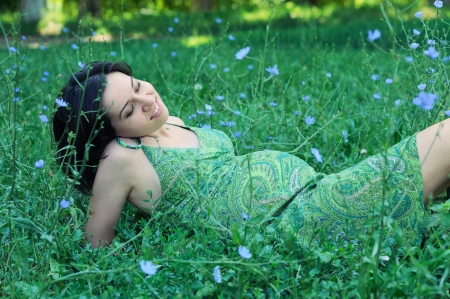 Beautiful pregnant woman relaxing on grass. Stock Photo - 17543622