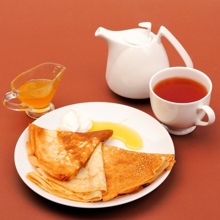 Pancakes with honey and tea served on a table. photo