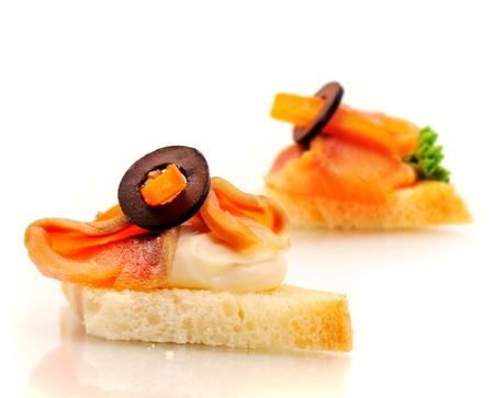 Sandwich sur pain de blé avec du saumon, crème et olive.