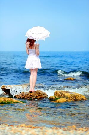 girl in white dress with umbrella on a beach photo