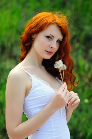 Redhead girl with dandelions, outdoor  photo