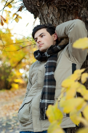 Young dreaming man standing in autumn park   photo