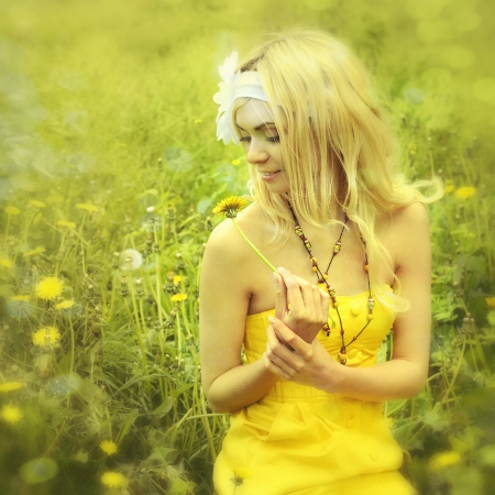 Beautiful young girl with long blond hair sitting in field with camomiles. photo