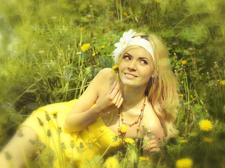 Young girl in yellow dress lying in field with camomiles, soft focus. photo