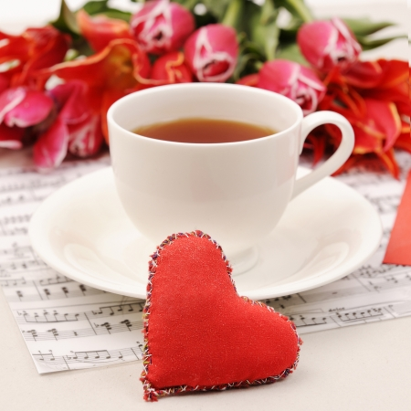 Cup of tea with toy heart and flowers. Valentine soft focus background.  photo