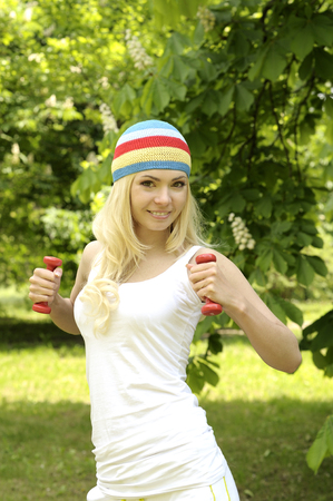 Blonde smiling sporty girl working out outdoor in park. photo
