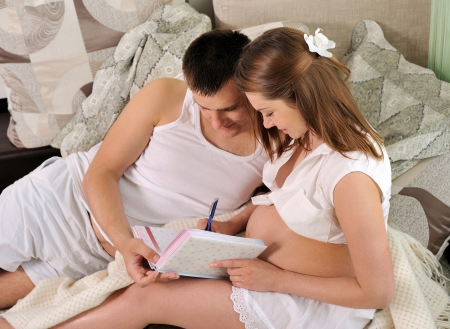 Pregnant woman and her husband writing the pregnancy diary on the sofa at home.