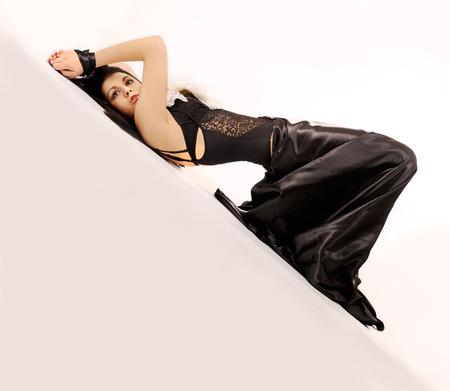 tied hair: Attraente donna obbligatorio vestita in posa nero su sfondo bianco.