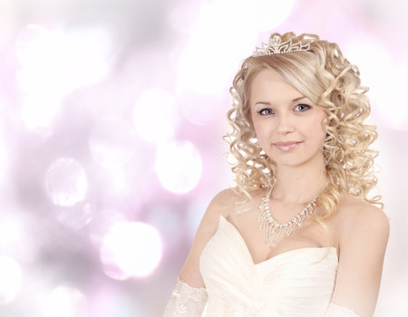Portrait of a smiling young bride on light bokeh  background. photo