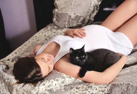 Young smiling pregnant woman with cat at home.