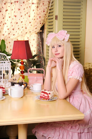 Young beautiful woman dressed in pink lace dress with cake.  photo